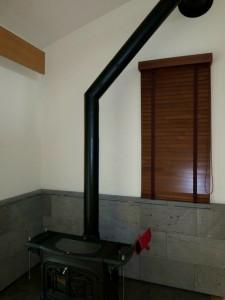 暖炉後ろの小窓へブラウンの木製ブラインドを配置、温かみのある落ち着いた空間へ